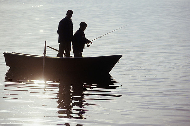 Silhouettes of father and son (13-14) standing in boat fishing