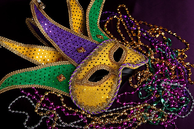 Mardi gras jester's mask with beads on a black background