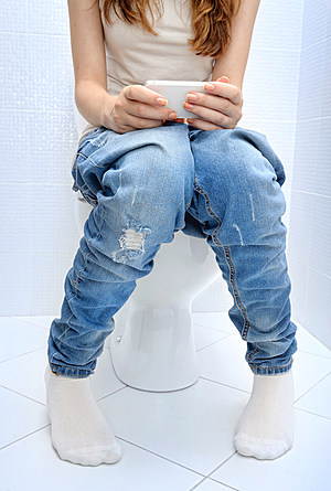 Young woman sitting  wc toilet bowl using phone in hands .