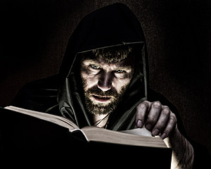 necromancer casts spells from thick ancient book by candlelight on